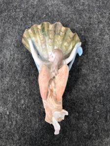 Bénitier en porcelaine bisque représentant un ange aux épaules tenant la coupe coquille.Italie.
