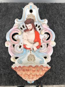 Bénitier en porcelaine percée de bisque à motifs rocaille et demi-longueur de Christ noué.
