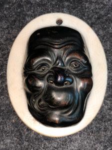 Petit masque avec une figure masculine en bronze grotesque.Japon