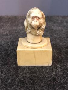 Petite sculpture en ivoire représentant un singe accroupi sur une base carrée.