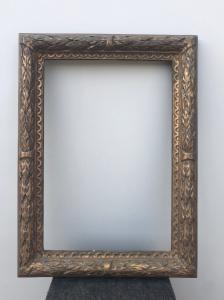 Cadre en bois sculpté et doré à motifs végétaux en relief.