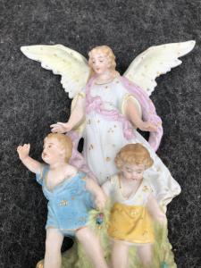 Bénitier en porcelaine bisque à figure d'ange aux ailes déployées protégeant deux enfants.