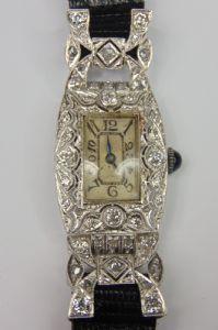"""Soirée déco horloge, en or blanc avec diamants et rosettes, avec prononcé mouvement de forme """"Longines"""" et le saphir cabochon sur la couronne"""