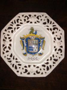 Planche à découper octogonale en majolique avec chantournage et armoiries nobles.