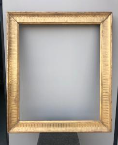 Monture en bois sculpté et feuille d'or avec motifs géométriques gravés.